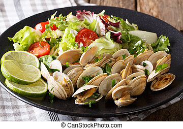 Delicious clams with greens and mix vegetable salad close-up. horizontal