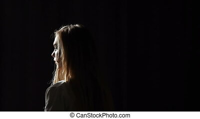 Portrait of a young woman against dark background. Studio...