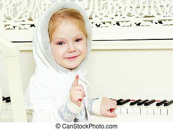 The little girl is waving a pen. - A cute little blonde is...