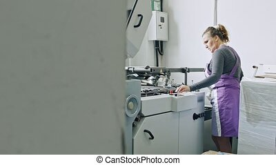 A female worker completes a paper for a magazine - manual...