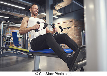 Male athlete working on rowing machine