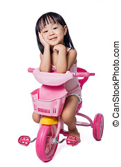 Asian chinese little girl riding a toy tricycle in isolated...