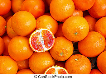 oranges and an orange cut in the stall of greengrocer -...