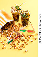 close up view of popcorn, iced tea and 3D glases on yellow,...
