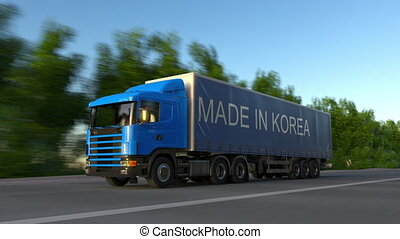 Speeding freight semi truck with MADE IN KOREA caption on the trailer. Road cargo transportation. Seamless loop 4K clip
