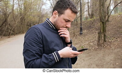 Man in park with mobile phone