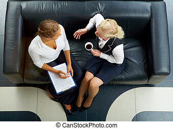 Females at work - Above angle of two friendly employees...