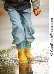 Running down puddles - Legs of happy lad running down puddle...