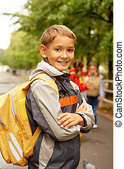 Going to school - Portrait of happy lad with rucksack on...