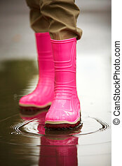 Autumn theme - Legs of child in rainboots standing in puddle