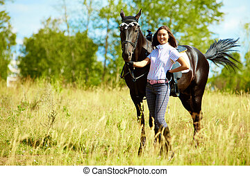 Active female - Image of happy female with purebred horse...