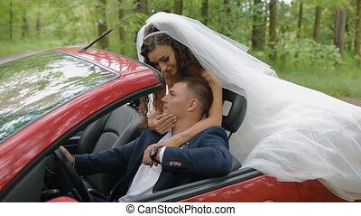 Bride and groom in red cabriolet. Young people kiss each...