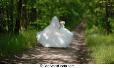 Happy bride jumping on the path in the wood - Happy...