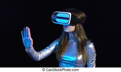 Cyber young woman in silver clothing wearing virtual reality...