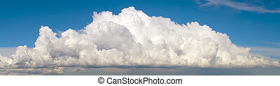 Blue sky with big fluffy cumulus cloud wide panoramic background.