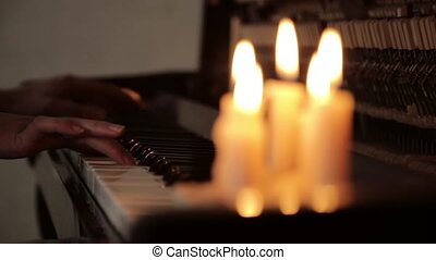 close-up female hands playing piano on a dark in a candles...