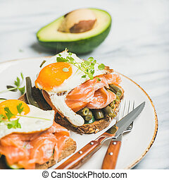 Salmon, avocado, fried egg, beans and sprouts sandwiches,...
