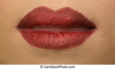 The girl sexually licks lips with red lipstick. - The girl...