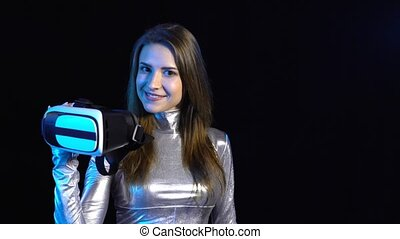 Cyber young woman in silver clothing showing virtual reality googles