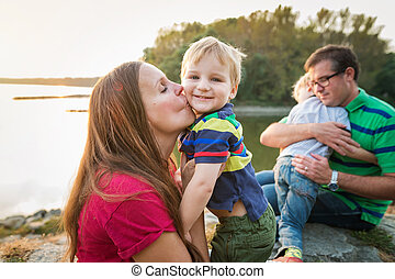 Family with two boys at the lake, sunny spring day. Parents...