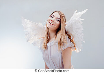 An angel from heaven. Young, wonderful blonde girl in the image of an angel with white wings.