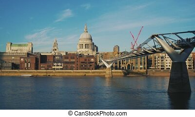 View to the City of London, Millennium Bridge and Saint Paul's Cathedral from Thames embankment. With red construction crane.
