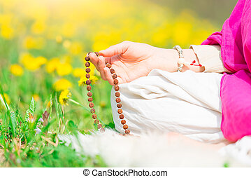 Recitation of mantras holding the mala during a yoga...