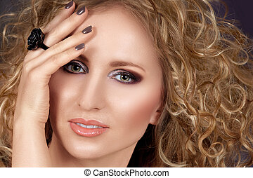beautiful blond woman with long curly hair and smoky...
