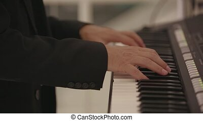 A man plays an electronic piano at a wedding.