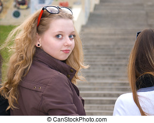 Looking back - Teenage blond haired girl looking back over...