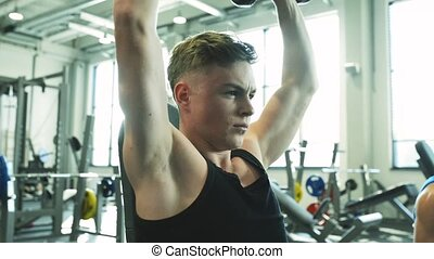 Handsome man in gym working out with weights - Young...