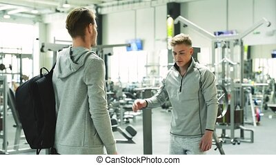 Two young fit men in gym greeting each other. - Two young...