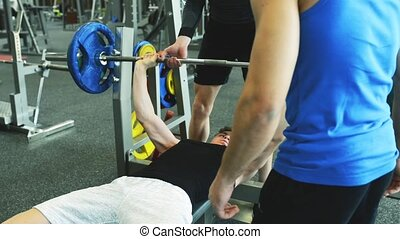 Men in gym doing high five after finishing bench presses. -...