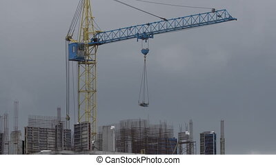 Construction site. Crane lifts cargo to floor.