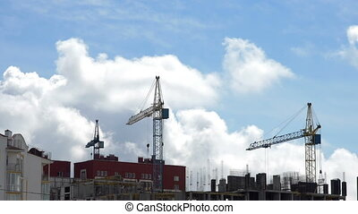 Construction site against a blue sky with floating clouds.