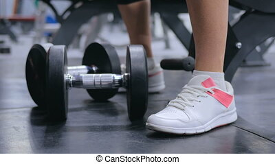 Close up shot of athletic young woman lifting dumbbells at...