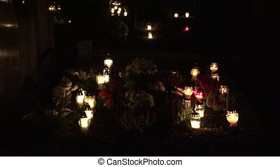 cemetery decorated with candles for All Saints Day at night. blur out.