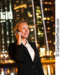 Smiling young business woman talking on the phone in the big city at night