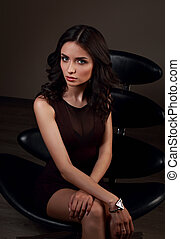 Sexy young model in brown dress sitting on the black chair on dark shadow background with fashion watch on the hand