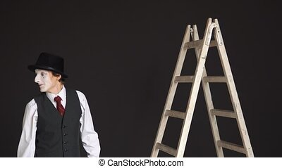 Man mime climbs the ladder up, looks around.