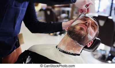 man and barber with straight razor shaving beard - beauty,...