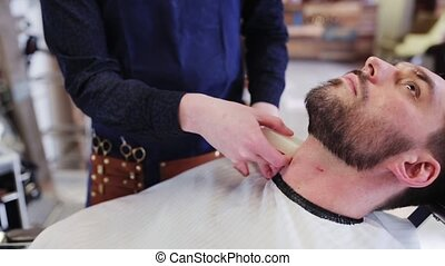 barber treating male neck with alum bar at shop - beauty,...