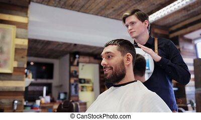 man and hairdresser with mirror at barber shop - beauty,...