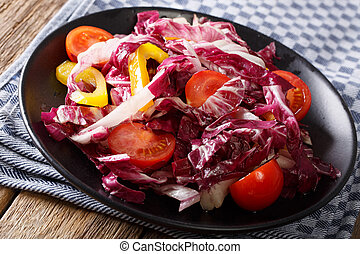 Healthy radicchio salad with tomatoes and pepper closeup....