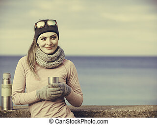 Fit woman in cold day warming up drink tea - Woman athlete...