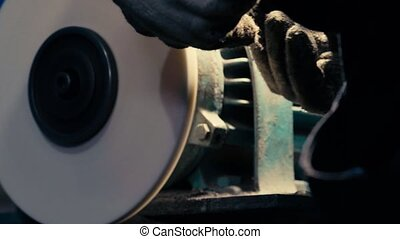 Man's hands working with a circular grindstone - Close up of...