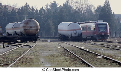 Train passes by broken tank,two shots