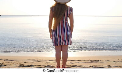 Happy woman standing by the water with arms raised on the beach