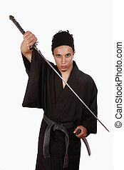 Youg martial artist practicing Iaido with a sword and with...