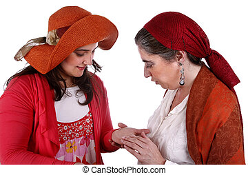 Gypsy woman reading the lines in a young woman's hand
